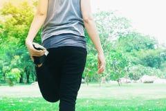 Donna asiatica di forma fisica che allunga le gambe prima dell'allenamento, stile di vita sano Immagini Stock Libere da Diritti