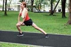 Donna asiatica di Happines che allunga le sue gambe prima del funzionamento in parco Concetto di esercizio e di forma fisica fotografia stock libera da diritti