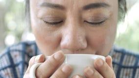 Donna asiatica di mezza età che si siede in un caffè con una tazza di tè o caffè ed inghiottire Primo piano delle mani con una ta stock footage