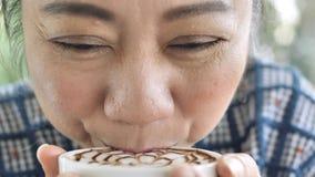 Donna asiatica di mezza et? che si siede in un caff? con una tazza di t? o caff? ed inghiottire Primo piano delle mani con una ta stock footage