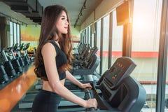 Donna asiatica di sport che cammina o che corre sull'attrezzatura della pedana mobile nella f Immagini Stock