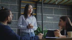 Donna asiatica di Yong che parla e che discute le nuove idee con il gruppo creativo durante il 'brainstorming' dei progetti start video d archivio