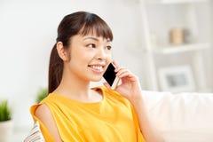 Donna asiatica felice che rivolge allo smartphone a casa Immagine Stock Libera da Diritti