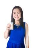 Donna asiatica felice con bicchiere di latte a disposizione isolato sulla b bianca fotografia stock