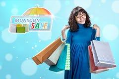 Donna asiatica felice con i molti sacchetto della spesa sulla vendita di monsone fotografia stock