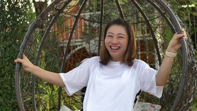 Donna asiatica felice sulle oscillazioni in un parco stock footage