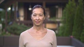 Donna asiatica invecchiata media che mostra i pollici sul segno fuori video d archivio