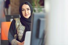 Donna asiatica musulmana che lavora nell'ufficio con il computer portatile fotografia stock libera da diritti