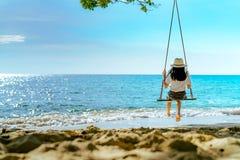 Donna asiatica nell'oscillazione del cappello di usura di stile casuale le oscillazioni alla spiaggia di sabbia ed a sembrare il  immagini stock libere da diritti