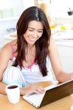 Donna asiatica positiva che per mezzo del suo computer portatile nel paese Fotografia Stock Libera da Diritti