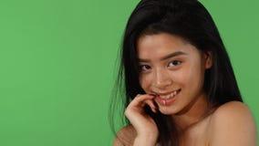 Donna asiatica sbalorditiva che morde il suo dito che sorride seducente alla macchina fotografica video d archivio