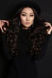 Donna asiatica sensuale con capelli scuri lunghi in vestito nero Immagine Stock