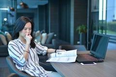 Donna asiatica sollecitata di affari casuali che legge un libro davanti a Immagine Stock