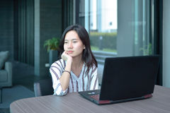 Donna asiatica sollecitata di affari casuali che pensa davanti al lapto Fotografie Stock Libere da Diritti