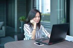 Donna asiatica sollecitata di affari casuali che utilizza un computer portatile nel condominio, GE Immagini Stock Libere da Diritti