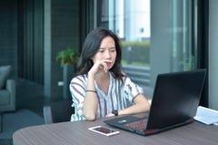 Donna asiatica sollecitata di affari casuali che utilizza un computer portatile nel condominio, GE Fotografie Stock Libere da Diritti
