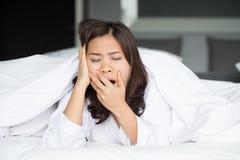 Donna asiatica sonnolenta che sbadiglia a letto Fotografie Stock