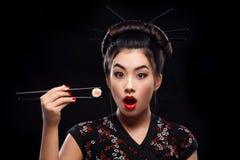 Donna asiatica sorpresa che mangia i sushi ed i rotoli su un fondo nero Fotografia Stock