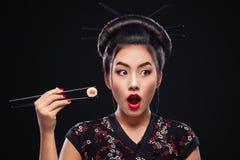 Donna asiatica sorpresa che mangia i sushi ed i rotoli su un fondo nero Fotografie Stock