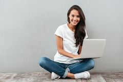 Donna asiatica sorridente che lavora al computer portatile Fotografia Stock