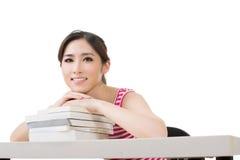 Donna asiatica sorridente con i libri Fotografia Stock