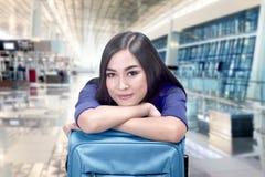 Donna asiatica sorridente con la partenza aspettante di volo della valigia Fotografie Stock