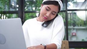 Donna asiatica sorridente dei bei giovani che lavora al computer portatile mentre godendo utilizzando smartphone nel salone a cas archivi video