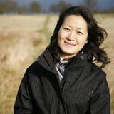 Donna asiatica sorridente del ritratto che esamina macchina fotografica Immagini Stock