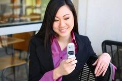 Donna asiatica Texting di affari con il telefono Fotografia Stock