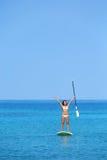 Donna Aspirational di stile di vita della spiaggia sul paddleboard Immagini Stock Libere da Diritti