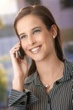 Donna astuta che per mezzo del telefono mobile Immagine Stock