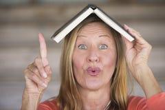 Donna astuta con il libro sulla testa e sull'idea Fotografie Stock Libere da Diritti