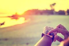 Donna astuta dell'orologio che usando il bottone e il touchscre commoventi dello smartwatch Fotografia Stock