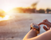 Donna astuta dell'orologio che usando il bottone e il touchscre commoventi dello smartwatch Immagini Stock