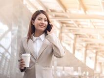 Donna astuta di affari in un vestito con il telefono cellulare Fotografie Stock Libere da Diritti