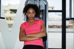 Donna atletica adatta che si appoggia la macchina della stampa mentre avendo un resto dopo l'allenamento Fotografia Stock Libera da Diritti
