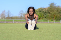 Donna atletica adatta che si rilassa su un campo sportivo Fotografia Stock Libera da Diritti
