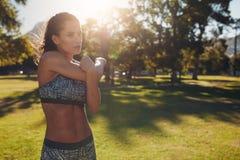 Donna atletica che allunga armi prima dell'allenamento Fotografia Stock