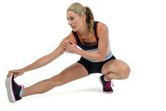 Donna atletica che allunga il suo tendine del ginocchio Immagine Stock Libera da Diritti