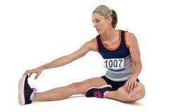 Donna atletica che allunga il suo tendine del ginocchio Fotografia Stock