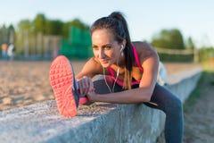 Donna atletica che allunga il suo tendine del ginocchio, forma fisica di addestramento di esercizio di gambe prima dell'allenamen Fotografie Stock