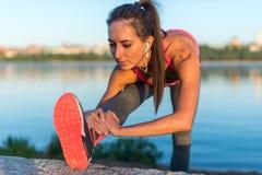 Donna atletica che allunga il suo tendine del ginocchio, forma fisica di addestramento di esercizio di gambe prima dell'allenamen Immagini Stock