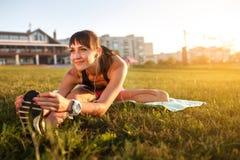 Donna atletica che allunga il suo tendine del ginocchio, forma fisica di addestramento di esercizio di gambe prima dell'allenamen Immagini Stock Libere da Diritti