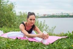 Donna atletica che allunga il suo tendine del ginocchio, forma fisica di addestramento di esercizio di gambe prima dell'allenamen Fotografia Stock