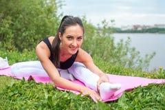 Donna atletica che allunga il suo tendine del ginocchio, forma fisica di addestramento di esercizio di gambe prima dell'allenamen Fotografie Stock Libere da Diritti