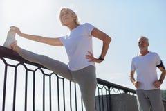 Donna atletica che allunga mentre il suo funzionamento del marito immagini stock libere da diritti