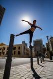 Donna atletica che equilibra sulla bitta e che la allunga fuori armi e gamba Fotografia Stock Libera da Diritti
