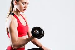 Donna atletica che fa allenamento di forma fisica con le teste di legno su fondo grigio Fotografie Stock Libere da Diritti