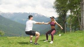 Donna atletica che fa esercizio con il suo partner maschio all'aperto sopra le alte montagne nel fondo archivi video