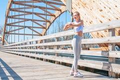 Donna atletica che fa scaldarsi ed allungamento delle sue armi prima dell'correre Fotografie Stock